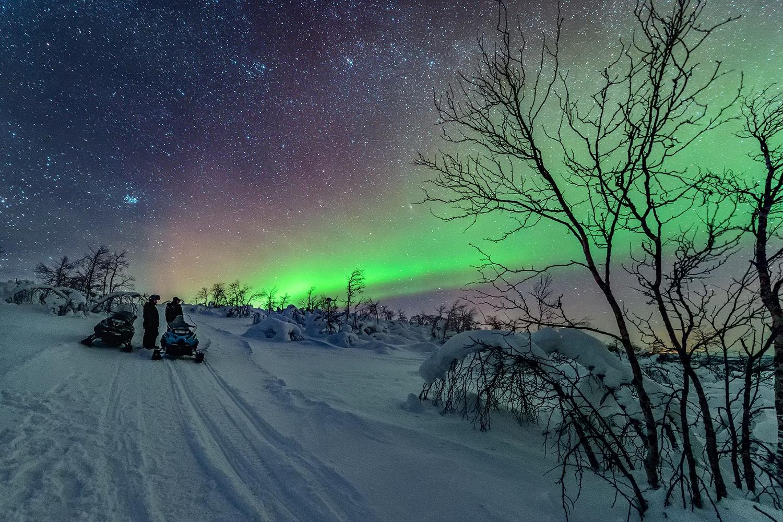 Snow mobiling under auroras
