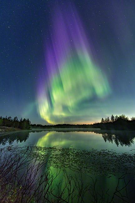 Aurora flame above a lake in autumn