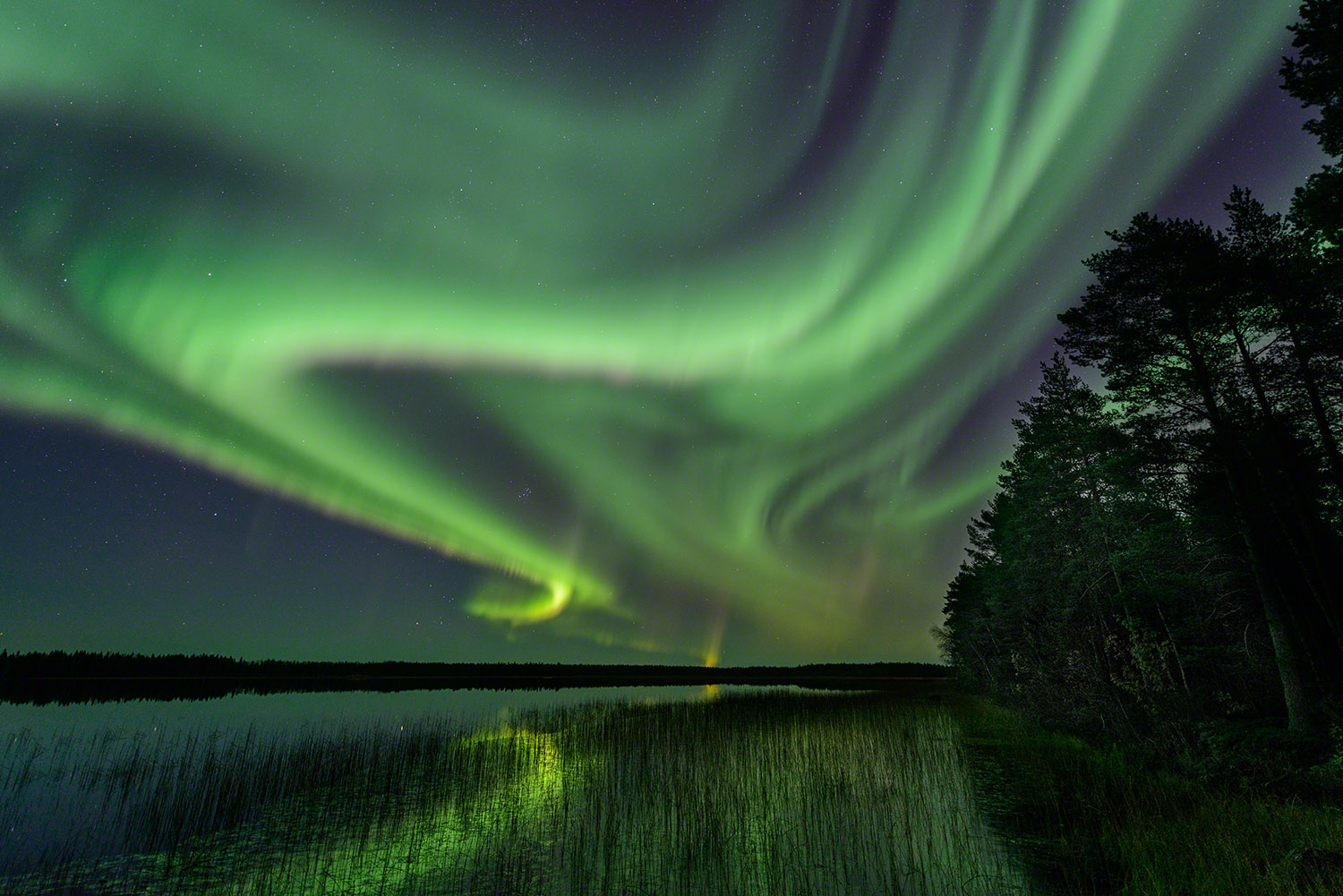 Aurora borealis photography with reflections in a lake near Oulu, Finland