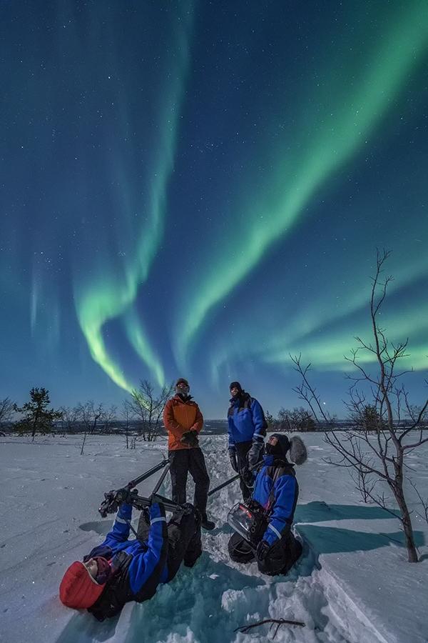 TV team gazing at the aurora borealis. Fernsehteam staunt über Polarlichter.